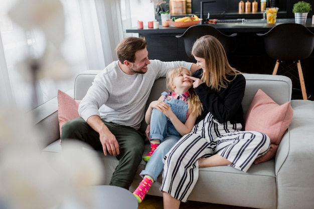 Padres abrazados con hija en el sofá