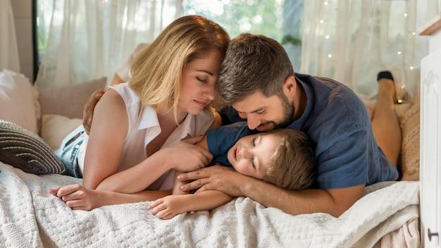 Padres abrazando a su hijo en la cama