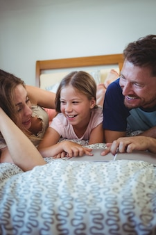 Padres acostados con su hija en la cama y mirando el álbum de fotos