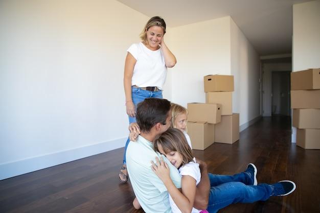 Padres alegres y dos hijas disfrutando de su nuevo hogar