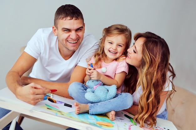 Padres alegres juegan con su hija en casa.