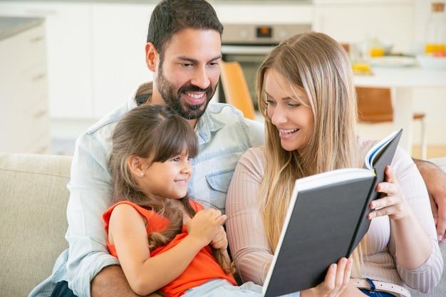 Padres alegres y niña de pelo negro sentados en el sofá en la sala de estar, leyendo un libro juntos y riendo.