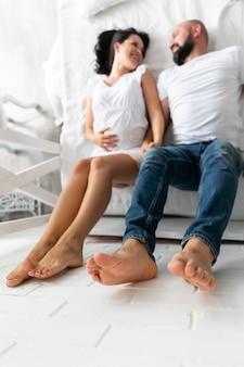 Padres de alto ángulo que permanecen en cama con los pies en la pared