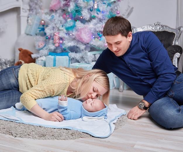 Padres amorosos abrazan a su bebé en una acogedora sala de estar. el concepto de navidad
