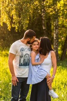 Padres amorosos besando a su hija en el parque