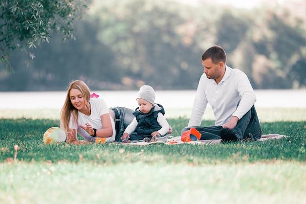 Padres amorosos y su pequeño hijo sentados en el césped en un día de verano. el concepto de paternidad