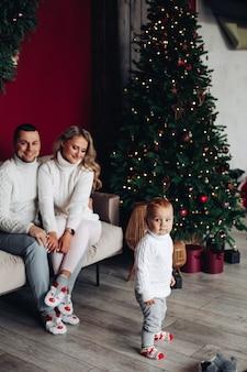 Padres amorosos vestidos de blanco sentados en el sofá cerca del árbol de navidad mientras miran a su hijo