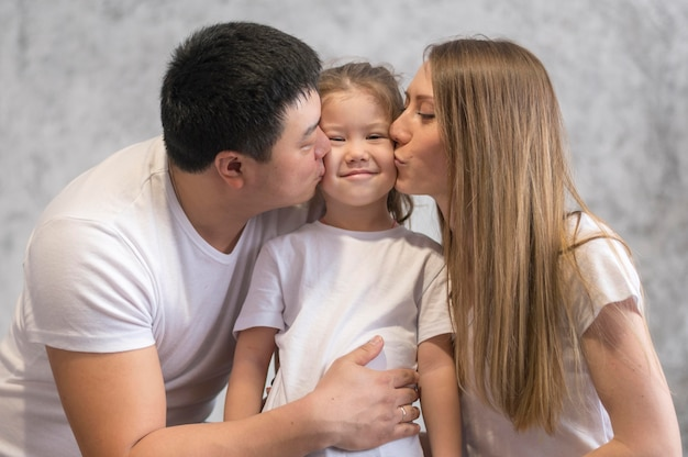 Padres de ángulo bajo besos niña