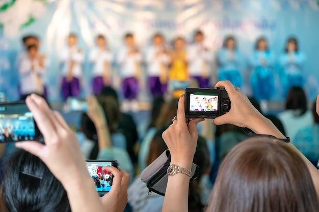 Padres asiáticos grabando vdo y sesión de fotos en el evento escolar de sus hijos, bangkok, tailandia.