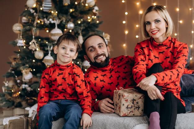 Los padres atractivos y su pequeño hijo en suéteres rojos se divierten abriendo regalos antes de navidad