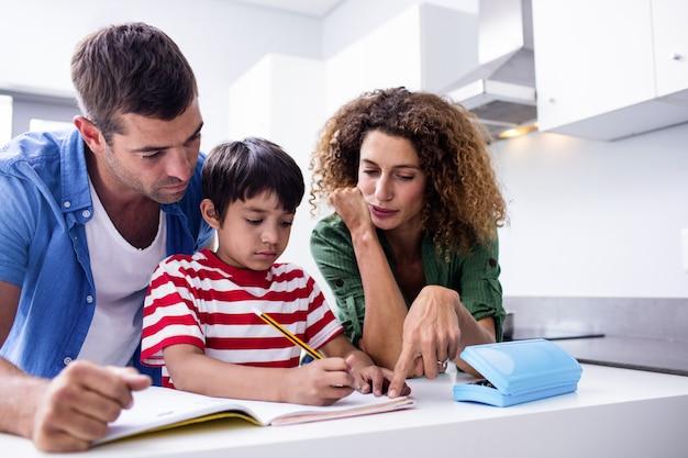 Padres ayudando a hijo con la tarea