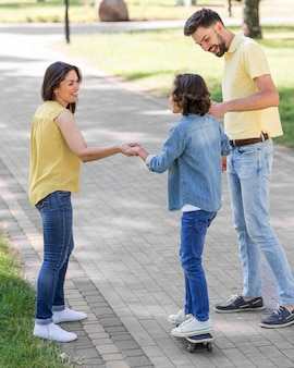 Padres ayudando a niño a usar patineta en el parque.