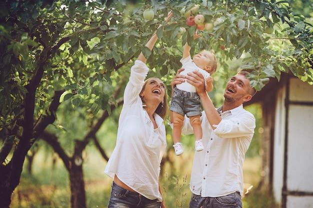 Los padres con el bebé disfrutando de un picnic en una granja con manzanos y cerezos.