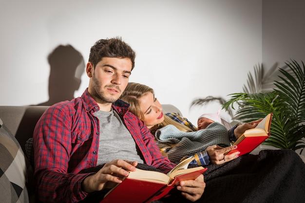 Padres con bebé leyendo libros en la noche.