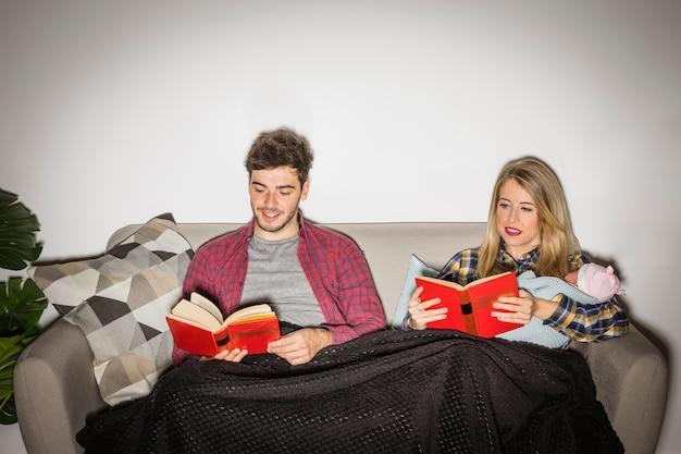 Padres con bebé leyendo libros