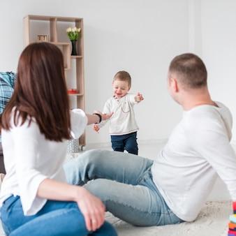 Padres con bebé sonriente en casa
