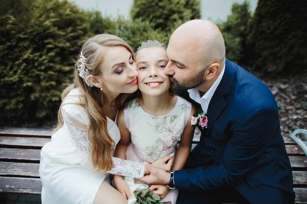Los padres besan a su hija en sus mejillas