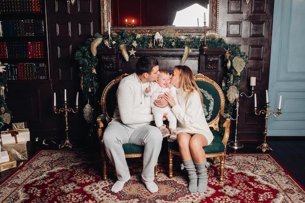 Padres besando al bebé en las mejillas. estudio decorado con velas, guirnaldas de abeto con adornos.