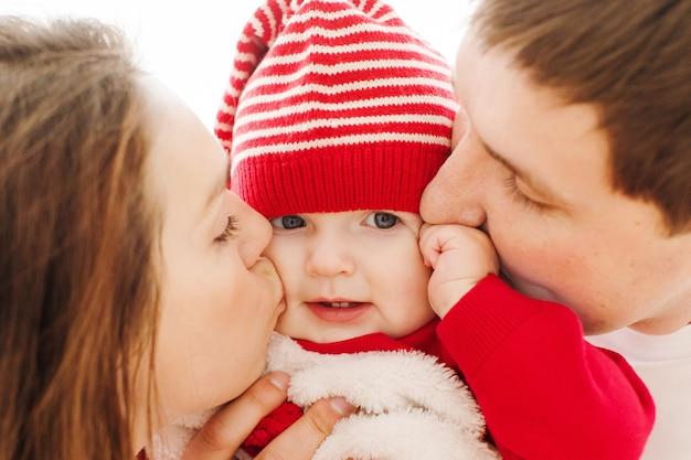 Padres besando bebe en mejillas