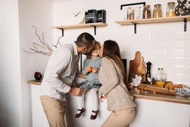 Padres besando a su hija en la cocina en casa.