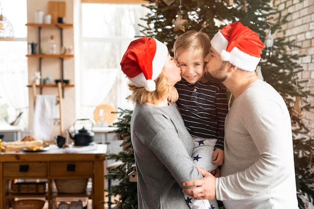 Padres besando a su hijo en las mejillas con espacio de copia
