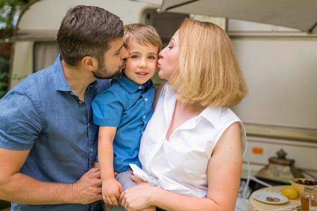 Padres besando a su hijo en las mejillas