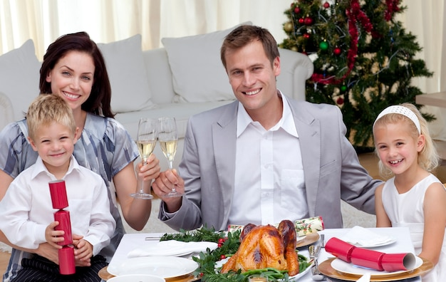 Padres brindando con vino en la cena de navidad.