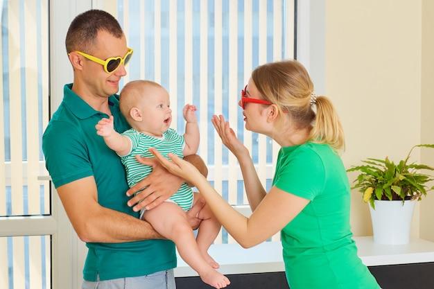 Padres en camisetas verdes con el bebé en sus brazos jugando juntos en una habitación con gafas de sol de colores.