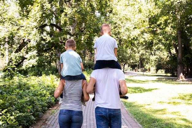 Padres cargando a sus hijos sobre los hombros.