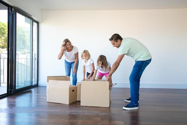 Los padres caucásicos desembalaje de cajas de cartón con hijas en una habitación vacía con balcón