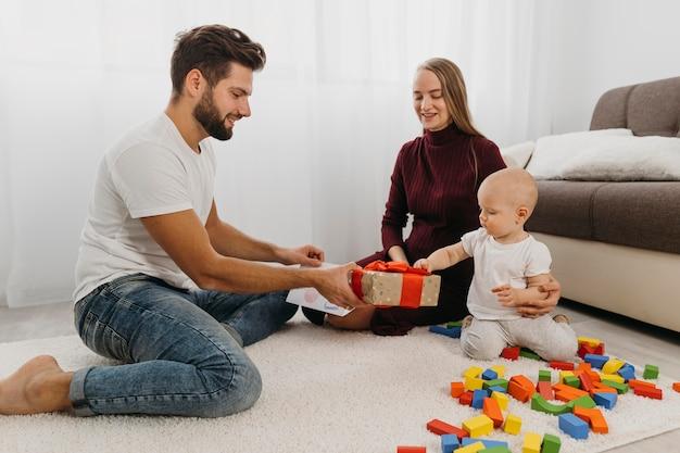 Padres dando regalo a su bebé en casa.