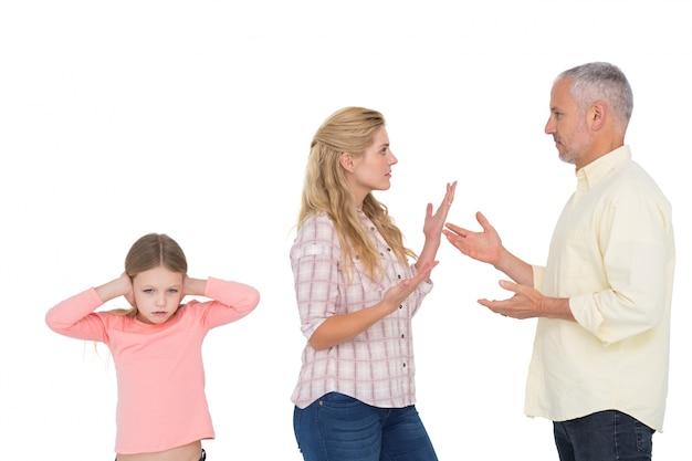 Padres discutiendo al lado de su hija molesta