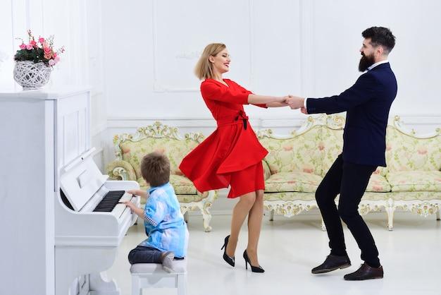 Los padres disfrutan del concepto de escuela de piano de la paternidad, el hijo del niño toca el instrumento musical de piano mientras los padres bailan los padres disfrutan de la paternidad, el concepto de educación familiar de músicos