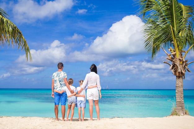 Los padres con dos hijos disfrutan de sus vacaciones en el caribe en la isla de antigua
