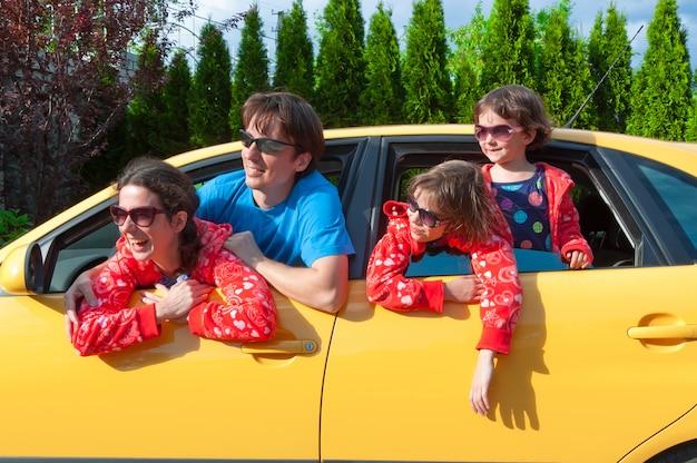 Padres con dos hijos que viajan en auto
