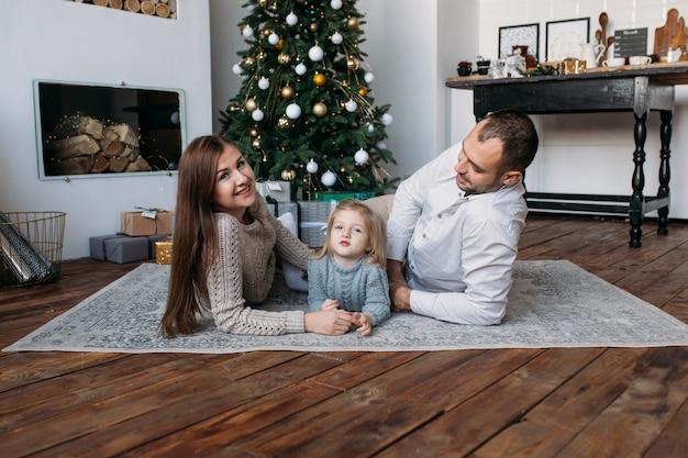 Padres e hija cerca del árbol de navidad en el interior