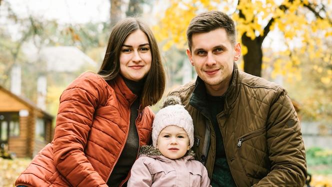Padres e hija pequeña que se sientan en el parque de otoño
