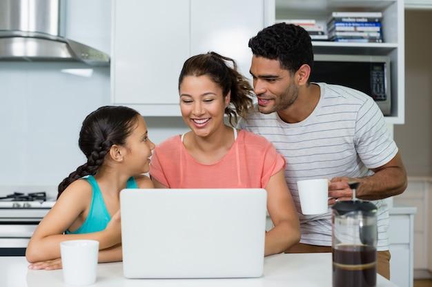 Padres e hija usando la computadora portátil en la cocina en casa