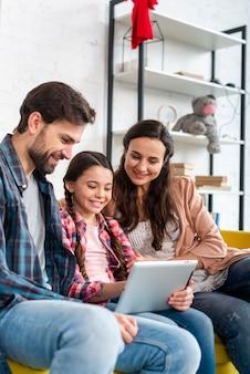 Padres e hija usando una computadora portátil