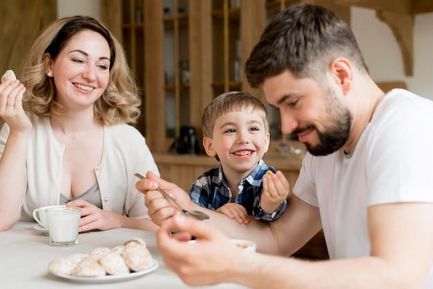 Padres e hijo comiendo dulces para el desayuno