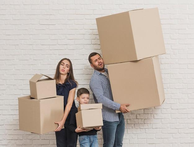 Padres e hijo sosteniendo cajas de cartón
