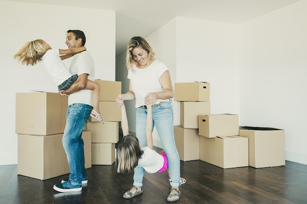Padres e hijos alegres que disfrutan del nuevo hogar, bailan y se divierten cerca de montones de cajas en una habitación vacía