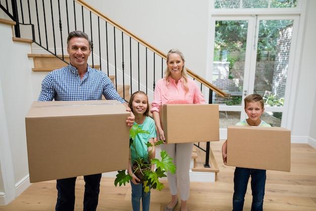 Padres e hijos con cajas de cartón en la sala de estar en casa