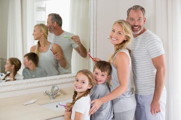 Padres e hijos cepillarse los dientes en el baño.