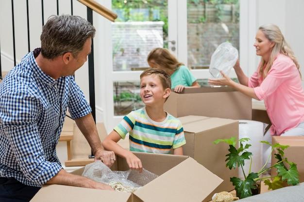 Padres e hijos desempacando cajas de cartón en la sala de estar
