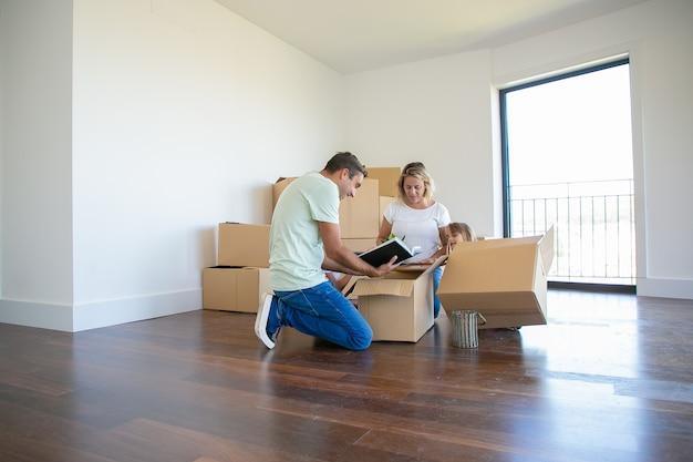 Padres e hijos desempacando cosas en un apartamento nuevo, sentados en el suelo y sacando objetos de la caja abierta