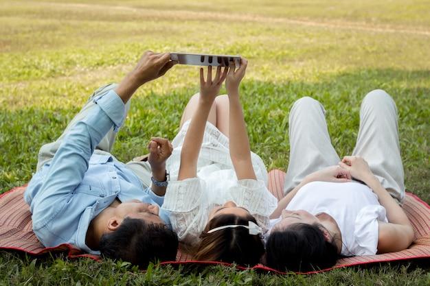 Padres e hijos están jugando la tableta en el tapete del parque.