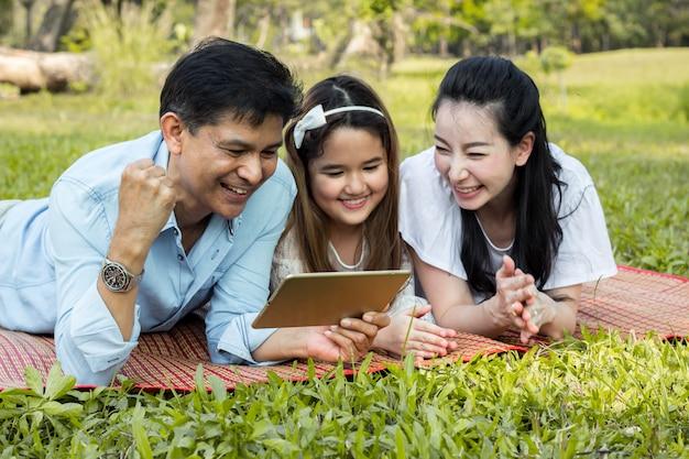 Padres e hijos están jugando la tableta en el tapete.