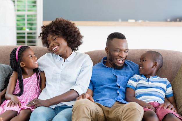 Padres e hijos interactuando sentados en el sofá de la sala de estar