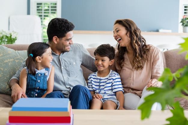 Padres e hijos interactuando en el sofá de la sala